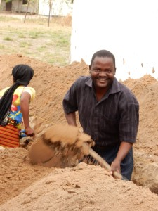 Care Centre manager Abdallah hard at work digging a trench to bring a water supply closer to the kindergarten.