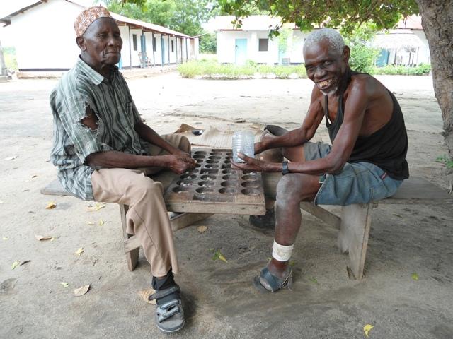 Mzee Mkambakamba playing Bao with a friend, a rather complicated Tanzanian board game